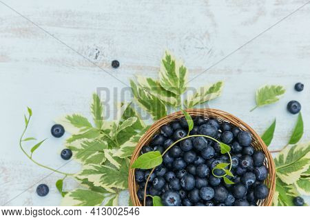 Fresh Blueberries In Basket With Leaves Pattern Top View. Healthy Food On White Table Mock Up. Delic