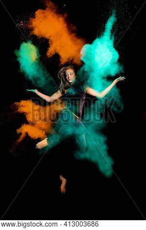 Expressive Girl Makes A High Jump With A Explosion Of Dry Colorful Holi Powder. Holi Colour Splash