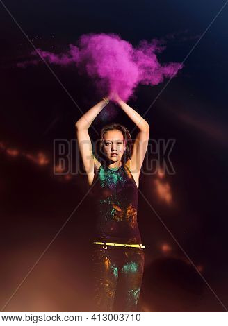 Young Woman Makes Hand Clap With Colored Holi Powder At Night. Holi Festival Color