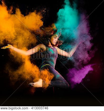 Expressive Young Woman Makes A High Jump With A Explosion Of Dry Colorful Holi Powder. Holi Colour S