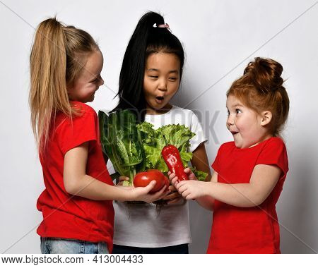 Children Like To Eat Well. Happy Little Girls Stand On A Gray Background With Fresh Vegetables And L