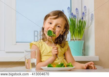 The Child Eats Broccoli With An Appetite. Organic Cabbage And Food On A Plate. Green Healthy Vegetab