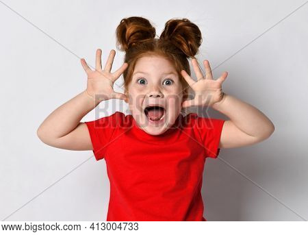Excited Little Girl With Freckles And Red Hair Screams Loudly With Raised Arms, Looking At The Camer