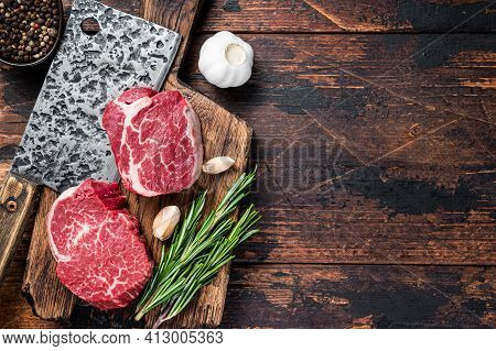 Fresh Raw Fillet Mignon Tenderloin Steaks On Butcher Cutting Board With Meat Cleaver. Dark Wooden Ba