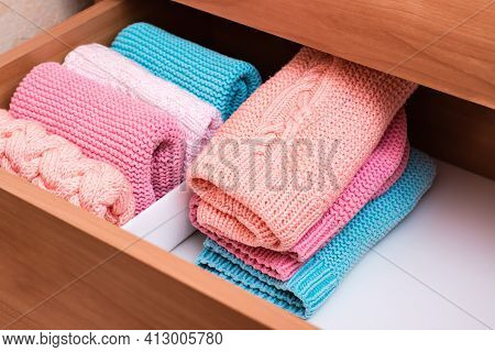 Organization And Order. A Stack Of Knitted Clothes Next To A Box Of Neatly Folded Items In A Dresser