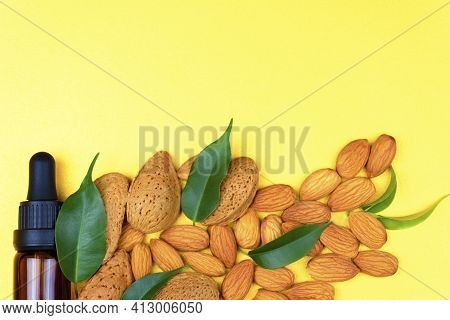 Almond Oil And Almonds On A Yellow Background. Organic Almond Oil.