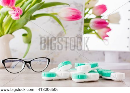 Low Vision And The Choice Between Glasses And Lenses. A Pile Of Containers For Lenses And Glasses In