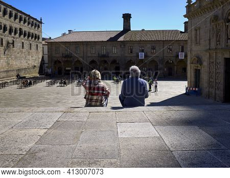 A Man And A Woman Contemplate A City Square Sitting On A Staircase