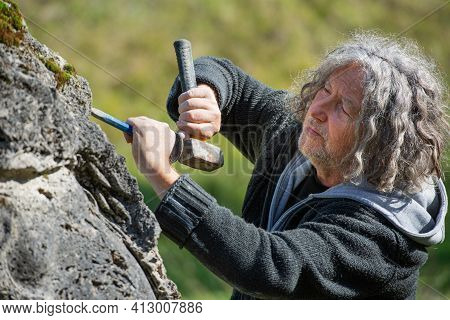 Senior Man, An Artist, Carving In Beautiful Natural Stone With A Chisel And Mallet.