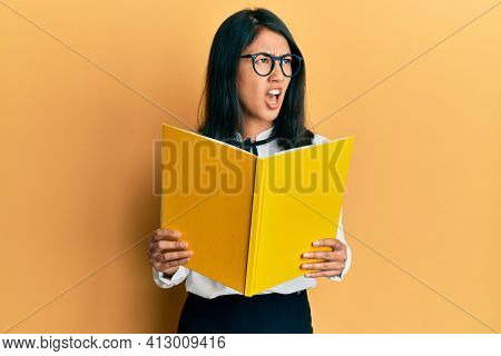 Beautiful asian young woman reading a book wearing glasses angry and mad screaming frustrated and furious, shouting with anger. rage and aggressive concept.