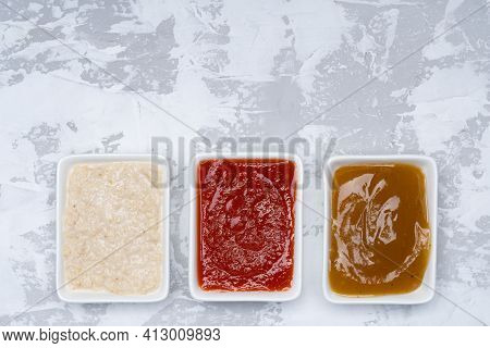 Three Kinds Of Sauces On A White Cement Background: Traditional Classic Ketchup, White Sauce, Sweet