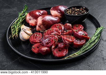 Sliced Raw Turkey Hearts Ready For Cooking. Black Background. Top View