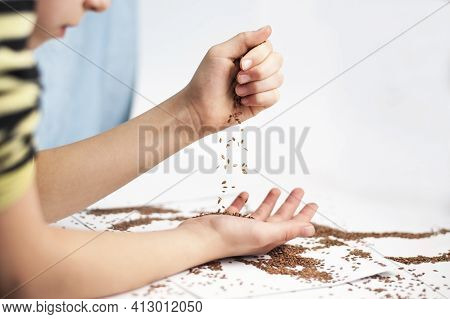 Young Girl Pours Grain Of Flax From One Hand To Another. She Is Going To Add The Grain Of Flax To Th