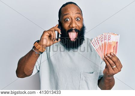 Young african american man having conversation talking on the smartphone holding norwegian krona banknotes sticking tongue out happy with funny expression.