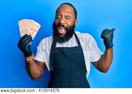 Young african american man wearing professional apron holding turkish liras banknotes pointing thumb up to the side smiling happy with open mouth