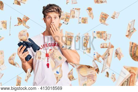 Young handsome man wearing lifeguard t-shirt using binoculars covering mouth with hand, shocked and afraid for mistake. surprised expression