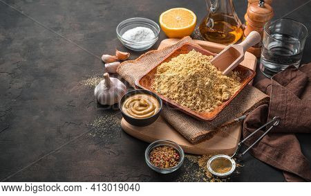 Mustard powder, ready-made mustard, spices, lemon, garlic and oil on a brown background. Side view with copy space. Cooking concept.