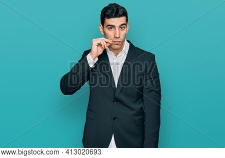 Handsome hispanic man wearing business clothes mouth and lips shut as zip with fingers. secret and silent, taboo talking