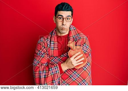 Handsome hispanic man wrapped in a winter blanket holding hot water bag puffing cheeks with funny face. mouth inflated with air, catching air.