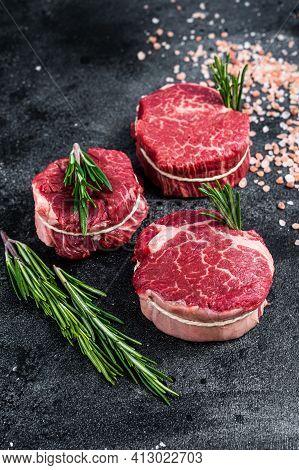 Fillet Mignon Tenderloin Raw Meat Beef Steaks On Butchery Table. Black Background. Top View