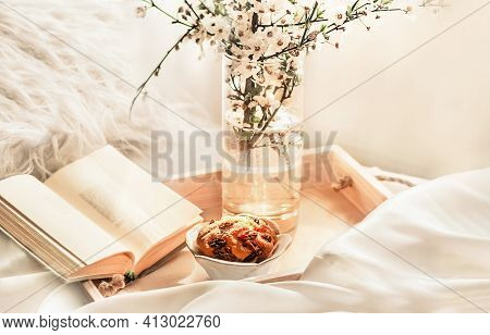 The Atmosphere Of A Romantic Morning, Breakfast In Bed. Flowering Branches In A Vase, An Open Book A