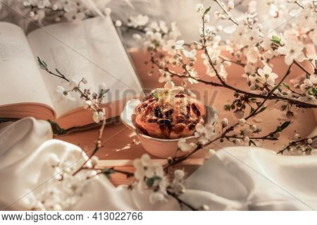 Flowering Branches, An Open Book And A Cupcake With Raisins On A Wooden Tray On A White Bed. Romanti