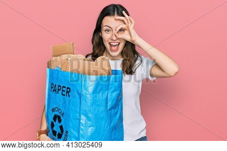 Young beautiful woman holding recycling wastebasket with paper and cardboard smiling happy doing ok sign with hand on eye looking through fingers