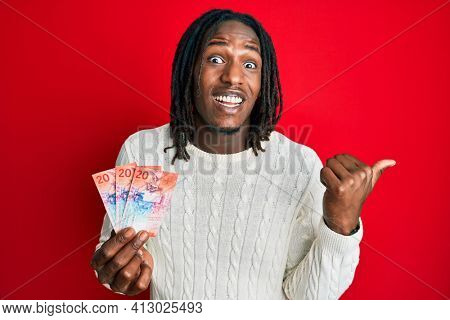African american man with braids holding 20 swiss franc banknotes pointing thumb up to the side smiling happy with open mouth