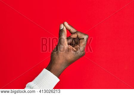 Arm and hand of african american black young man over red isolated background snapping fingers for success, easy and click symbol gesture with hand