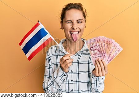 Young brunette woman holding thailand flag and baht banknotes sticking tongue out happy with funny expression.
