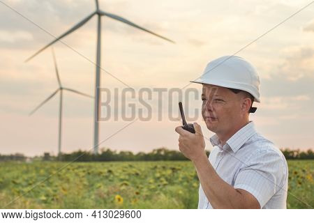 Construction Worker With Walkie-talkie Against Wind Turbine Farm. A Man In White Helmet Holding A Wa