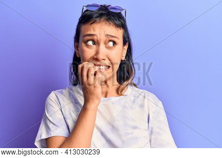 Young woman wearing casual clothes looking stressed and nervous with hands on mouth biting nails. anxiety problem.