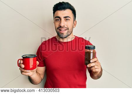 Young hispanic man holding cup of soluble coffee smiling with a happy and cool smile on face. showing teeth.