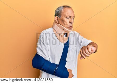 Handsome mature senior man wearing cervical collar and arm on sling checking the time on wrist watch, relaxed and confident