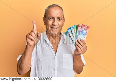 Handsome mature senior man holding swiss franc banknotes smiling with an idea or question pointing finger with happy face, number one