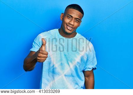 Young black man wearing tye die t shirt smiling happy and positive, thumb up doing excellent and approval sign