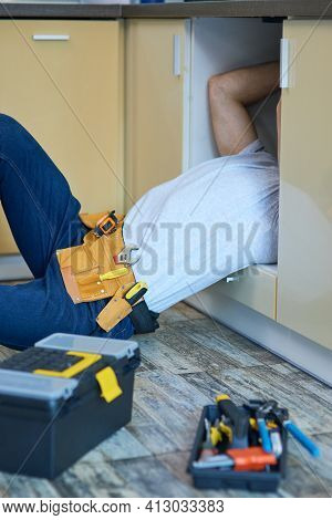 Get Fixed. Professional Plumber Wearing Tool Belt Examining And Fixing Sink Pipe Indoors. Tools And