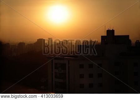 The Fall Of The Sun In The Middle Of The Buildings Of São Paulo. The Urban Sky Line Of São Paulo Ill
