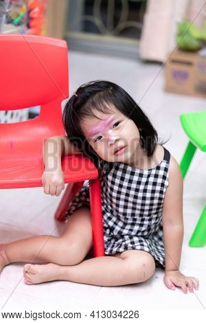 Asian Girl Is Leaning On Red Chair. Child Use Makeup To Imitate Adults. The Colors On Face Of Baby T