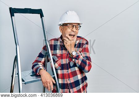 Handsome mature handyman close to construction stairs wearing hardhat laughing and embarrassed giggle covering mouth with hands, gossip and scandal concept