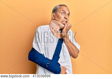 Handsome mature senior man wearing cervical collar and arm on sling looking stressed and nervous with hands on mouth biting nails. anxiety problem.