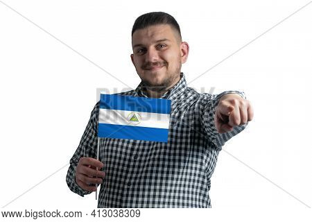 White Guy Holding A Flag Of Nicaragua And Points Forward In Front Of Him Isolated On A White Backgro
