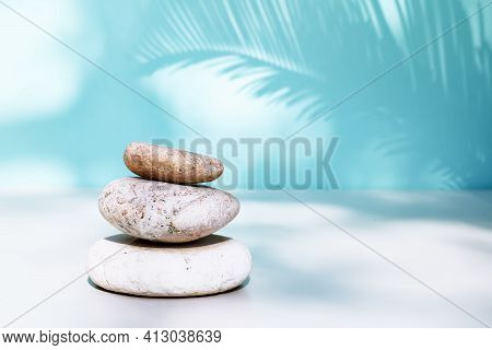 Three Grey Roundstones With A Shadow Of Palm Leaf On Pastel Turquoise Color Background. Spa Stones,