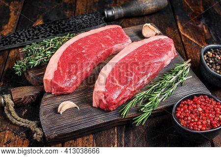 Raw Top Sirloin Beef Meat Steak On A Cutting Wooden Board. Dark Wooden Background. Top View