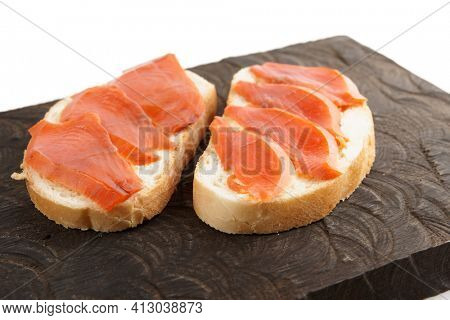 Two open-face sandwiches with smoked salmon on wooden board