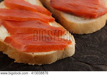 Open-face sandwiches with smoked trout on wooden board, close-up