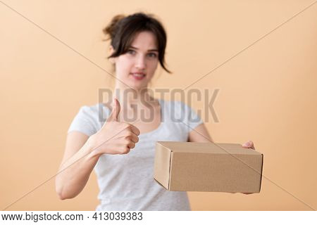 Young European Woman Advertises Cardboard Box In The Foreground, Gestures To The Quality With Her Fi