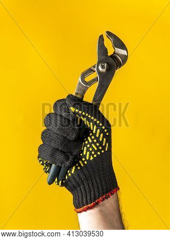A Raised Hand In Construction Glove Of A Master Plumber Holds Pliers Against Yellow Background. Sign