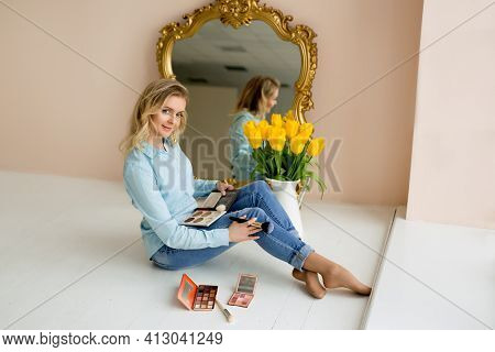 A Makeup Artist With A Brush And Makeup Sits At The Mirror. Content For The Makeup Artist. Young Bea