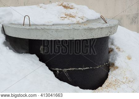 Black Concrete Ring Gray-buried Hatch In A Snowdrift Of White Snow On A Winter Street